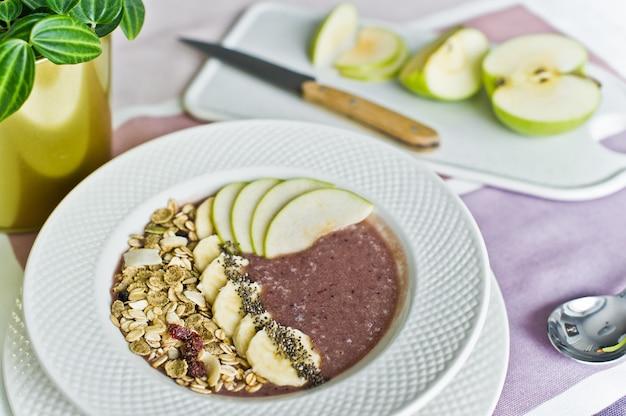 Tigela de batido com banana, maçã, sementes de chia, granola e iogurte.