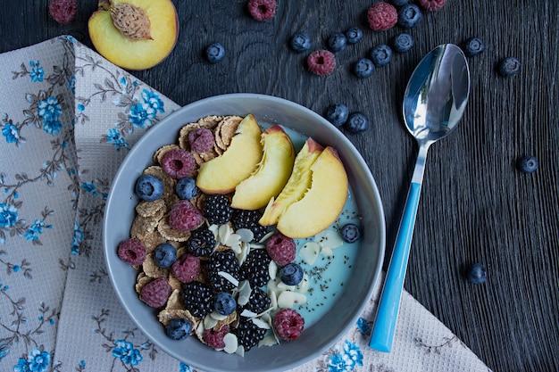 Tigela de batido com frutas frescas, sementes de chia, frutas e amêndoas. um conjunto de bagas framboesa, pêssego, mirtilos. café da manhã saudável.