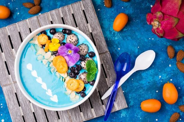 Tigela de batido com frutas, frutos, nozes e flores.