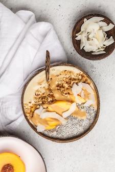 Tigela de batido com pudim de chia, pêssego, coco e granola em uma tigela de coco. café da manhã saudável do vegetariano, conceito limpo comer.