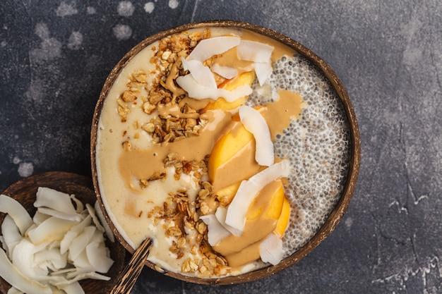 Tigela de batido com pudim de chia, pêssego, coco e granola em uma tigela de coco.