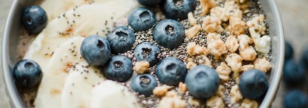 Tigela de batido de baga saudável café da manhã coberto com banana, granola, mirtilos e sementes de chia, com espaço de cópia