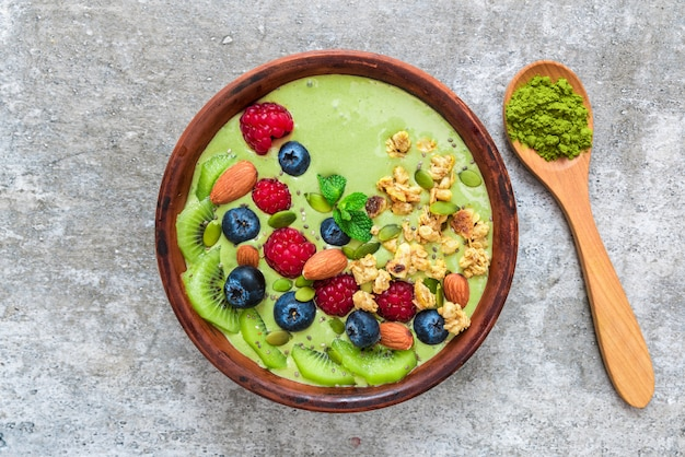 Tigela de batido de chá verde matcha com frutas frescas, nozes, sementes com uma colher para o café da manhã vegetariano saudável