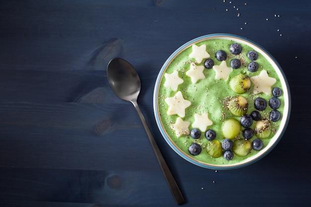 Tigela de batido de espinafre verde saudável com sementes de mirtilo, estrelas de banana, kiwi e chia