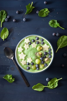 Tigela de batido de espinafre verde saudável com sementes de mirtilo, maçã, kiwi e chia