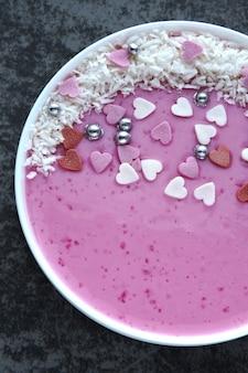 Tigela de batido rosa com decorações e corações para dia dos namorados.