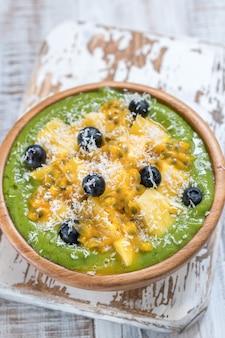 Tigela de batido verde com frutas e couve