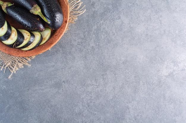 Tigela de berinjelas maduras frescas e fatias na superfície da pedra