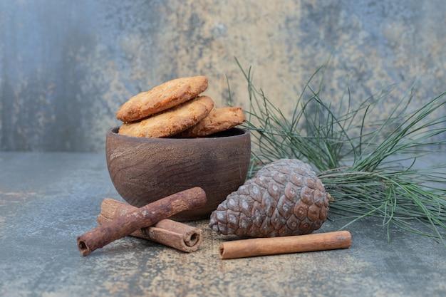Tigela de biscoitos, pinha e canela em fundo de mármore. foto de alta qualidade