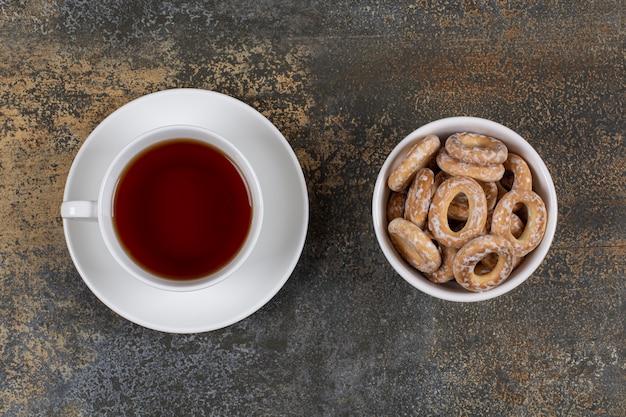 Tigela de biscoitos salgados e xícara de chá em mármore.