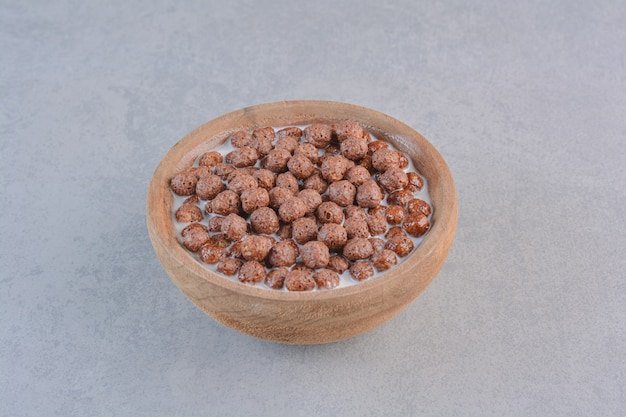 Tigela de bolas de cereais de chocolate com leite na mesa de pedra.