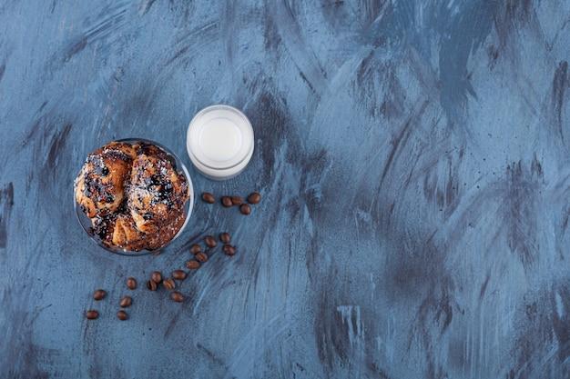 Tigela de bolo de canela delicioso e copo de leite no mármore.