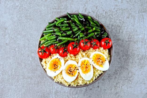 Tigela de buda com bulgur, feijão verde, tomate cereja e metades de ovo cozido. comida saudável em uma tigela. o conceito de nutrição dietética.