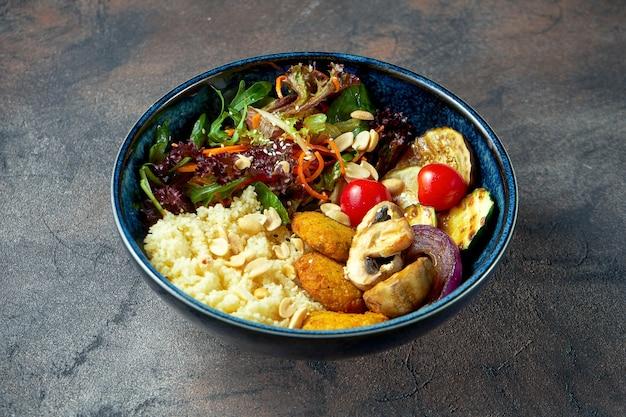 Tigela de buda com falafel, cuscuz e vegetais grelhados em um prato azul. foco seletivo