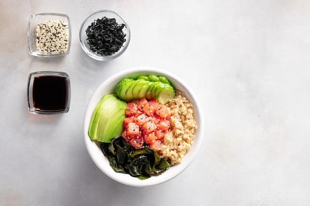 Tigela de buda com quinua, salmão, alga wakame, abacate e pepino. alimentos dietéticos.