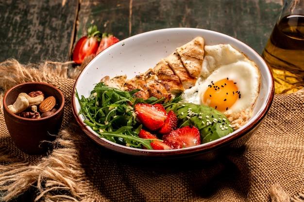 Tigela de buda com salada de frango com rúcula e morangos. fundo de receita de comida. fechar-se