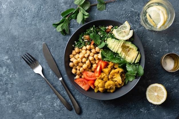 Tigela de buda comida equilibrada saudável vegetariana aloo gobi, grão de bico, tomate, abacate, espinafre de salada de tabule
