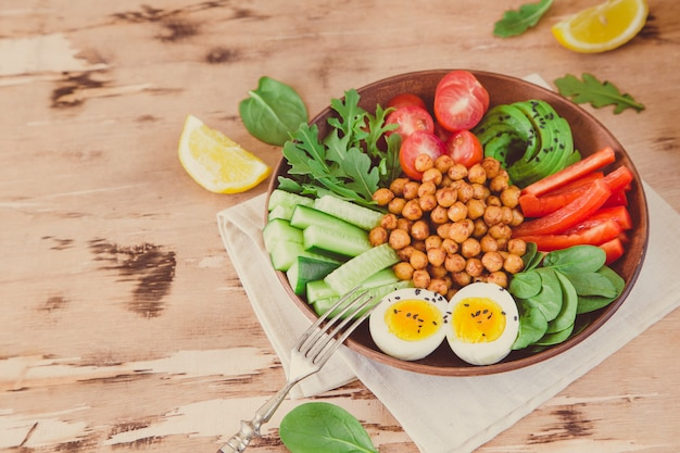 Tigela de buda, comida saudável e equilibrada. grão de bico frito, tomate cereja, pepino, páprica, ovos, espinafre, rúcula