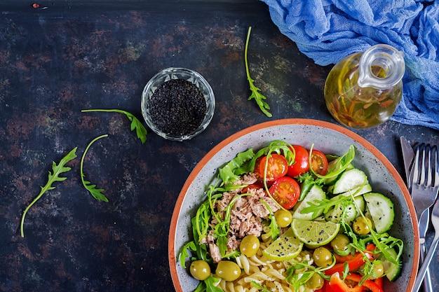 Tigela de buda. salada de macarrão com atum, tomate, azeitona, pepino, pimentão e rúcula em fundo rústico. vista do topo