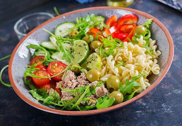 Tigela de buda. salada de macarrão com atum, tomate, azeitona, pepino, pimentão e rúcula em fundo rústico.