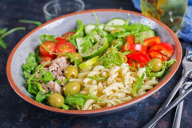 Tigela de buda. salada de macarrão com atum, tomate, azeitonas, pepino, pimentão e rúcula no fundo rústico