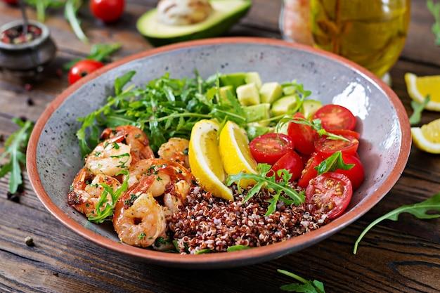 Tigela de buda saudável delicioso com camarão, tomate, abacate, quinoa, limão e rúcula