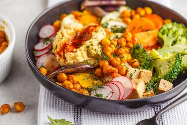 Tigela de buda vegan com legumes cozidos, grão de bico, hummus e tofu.