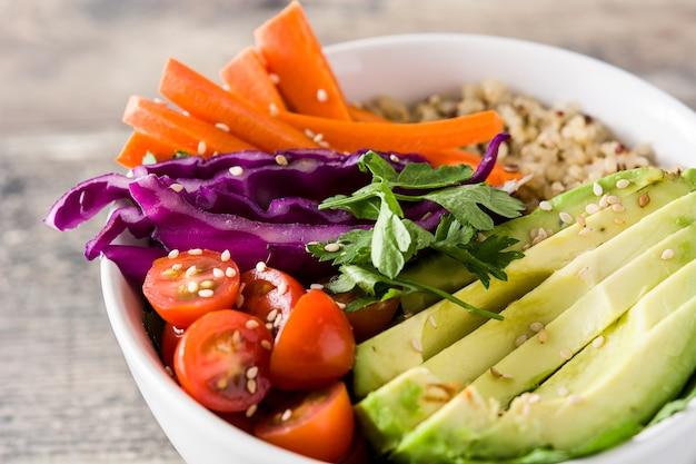 Tigela de buda vegan com legumes crus frescos e quinoa na mesa de madeira fechar