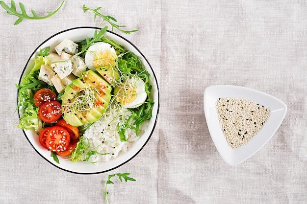 Tigela de buda vegetariano almoço com ovos, arroz, tomate, abacate e queijo azul na mesa.