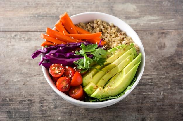Tigela de buda vegetariano com legumes crus frescos e quinoa na mesa de madeira.