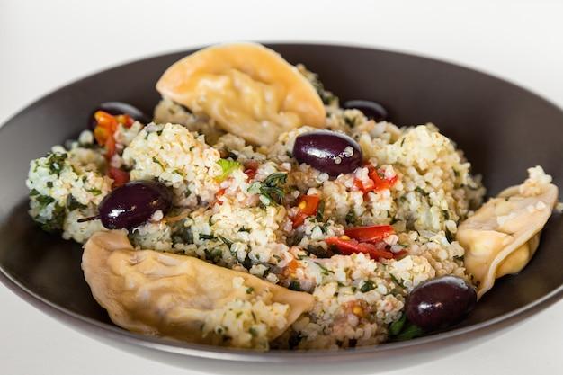 Tigela de bulgur de quinoa saudável com bolinhos de massa e azeitonas pretas