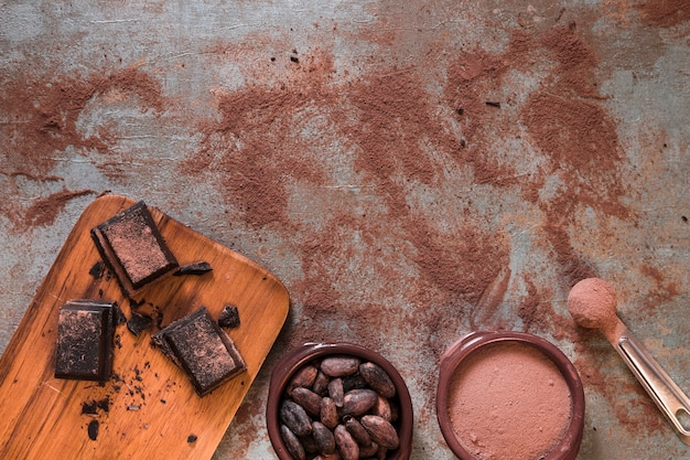 Tigela de cacau em pó e feijão com pedaços de chocolate na tábua de cortar