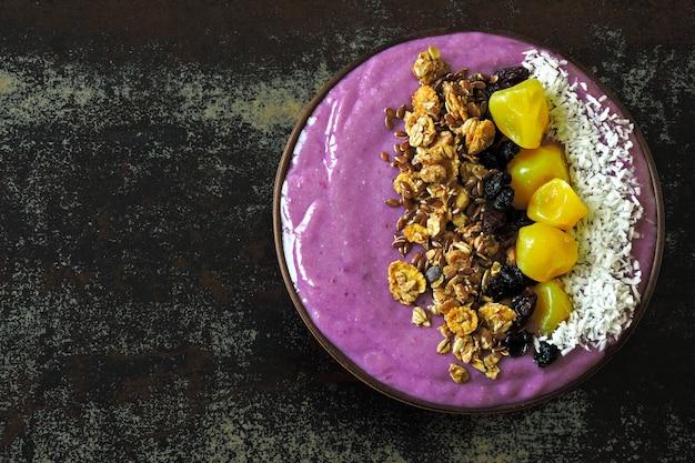 Tigela de café da manhã brilhante com batido de próton roxo e granola. smoothie de próton roxo.