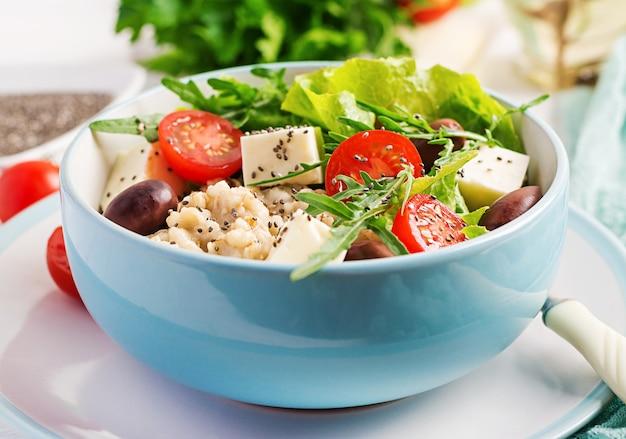 Tigela de café da manhã com aveia, tomate, queijo, alface e azeitonas. comida saudável. tigela de buda vegetariano