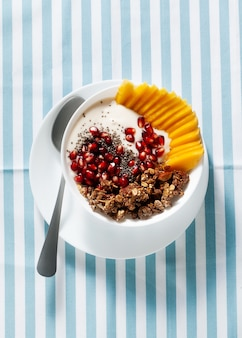 Tigela de café da manhã com granola, iogurte, manga doce fresca, sementes de chia, sementes de romã e xarope de bordo em um guardanapo listrado de azul
