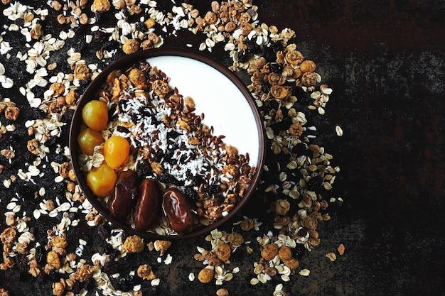 Tigela de café da manhã com iogurte grego, aveia, granola e frutas secas.