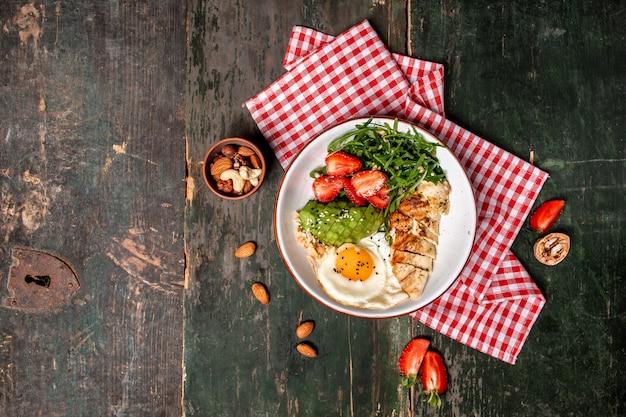 Tigela de café da manhã com salada de frango com rúcula e morangos. comida saudável. lugar para texto. vista do topo