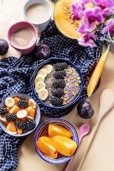 Tigela de café da manhã com sementes de aveia, iogurte, amoras, caqui, melão e chia, vista superior