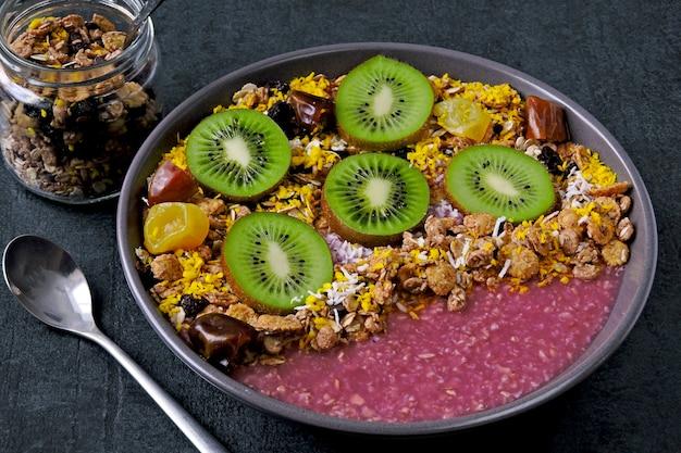 Tigela de café da manhã com smoothie de açaí, aveia, granola e frutas.