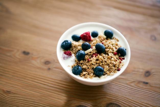 Tigela de café da manhã de iogurte delicioso com cereais e amoras frescas em uma mesa de madeira e toalha de cozinha de linho. conceito de nutrição saudável e orgânica. muesli de amora e framboesa. iogurte em uma tigela