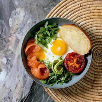 Tigela de café da manhã saudável com ovos fritos, salmão, abacate, tomate grelhado e salada, servindo com pão no guardanapo de palha sobre fundo de mármore escuro. postura plana, copie o espaço