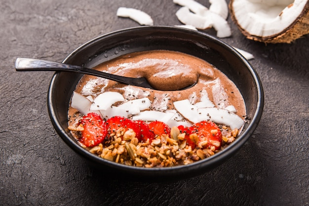 Tigela de café da manhã saudável. tigela de batido de banana de chocolate com flocos de coco, granola, morango.