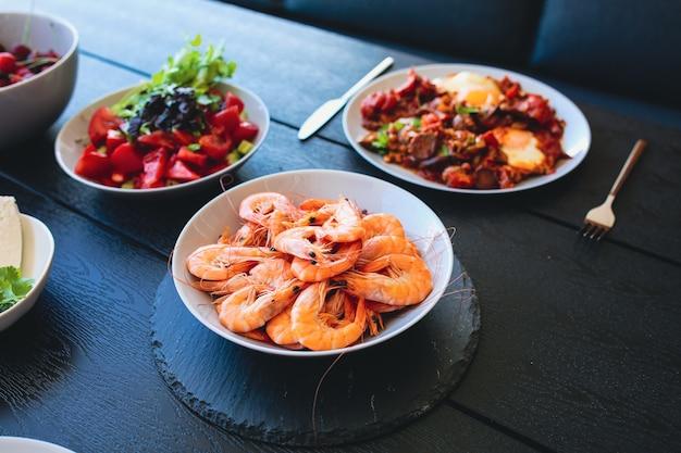 Tigela de camarão camarão rei camarão grande com camarão champanhe com camarão cerveja camarões à beira-mar frutos do mar deliciosos frutos do mar grelhados comida de verão na mesa comida na rua