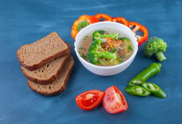 Tigela de canja de galinha, legumes e pão na superfície azul