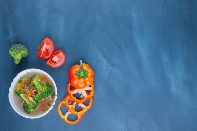 Tigela de canja de galinha, legumes e pão, sobre o fundo azul.