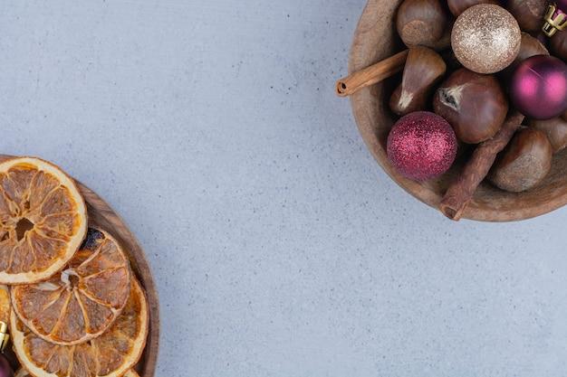 Tigela de castanhas com enfeites e laranjas secas.