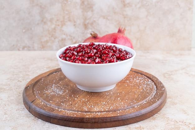 Tigela de cerâmica branca cheia de sementes frescas de romã