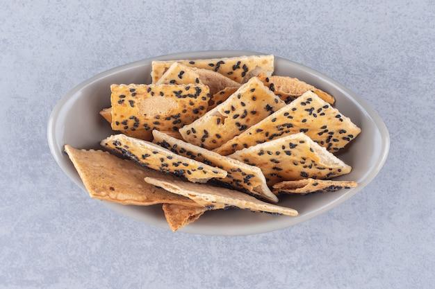 Tigela de cerâmica com biscoitos crocantes colocados em pedra
