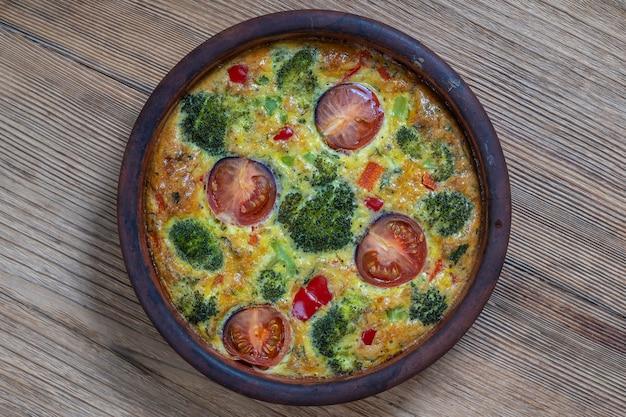 Tigela de cerâmica com fritada de vegetais, comida vegetariana simples. fritada com ovo, tomate, pimenta, cebola, brócolis e queijo na mesa de madeira, close-up. omelete de ovo italiano