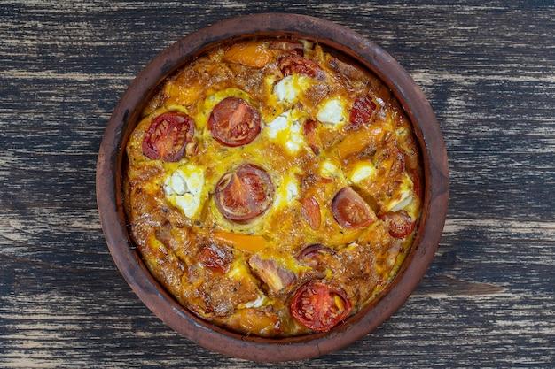 Tigela de cerâmica com fritada de vegetais, comida vegetariana simples. fritada com tomate, pimenta, cebola e queijo feta na mesa de madeira, close-up. omelete de ovo italiano, vista de cima